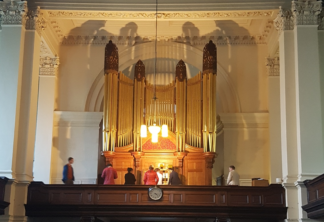Organ lit up and being played by music students