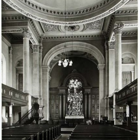 Historic view of nave, showing pews throughout the church, the east window and decorative plasterwork