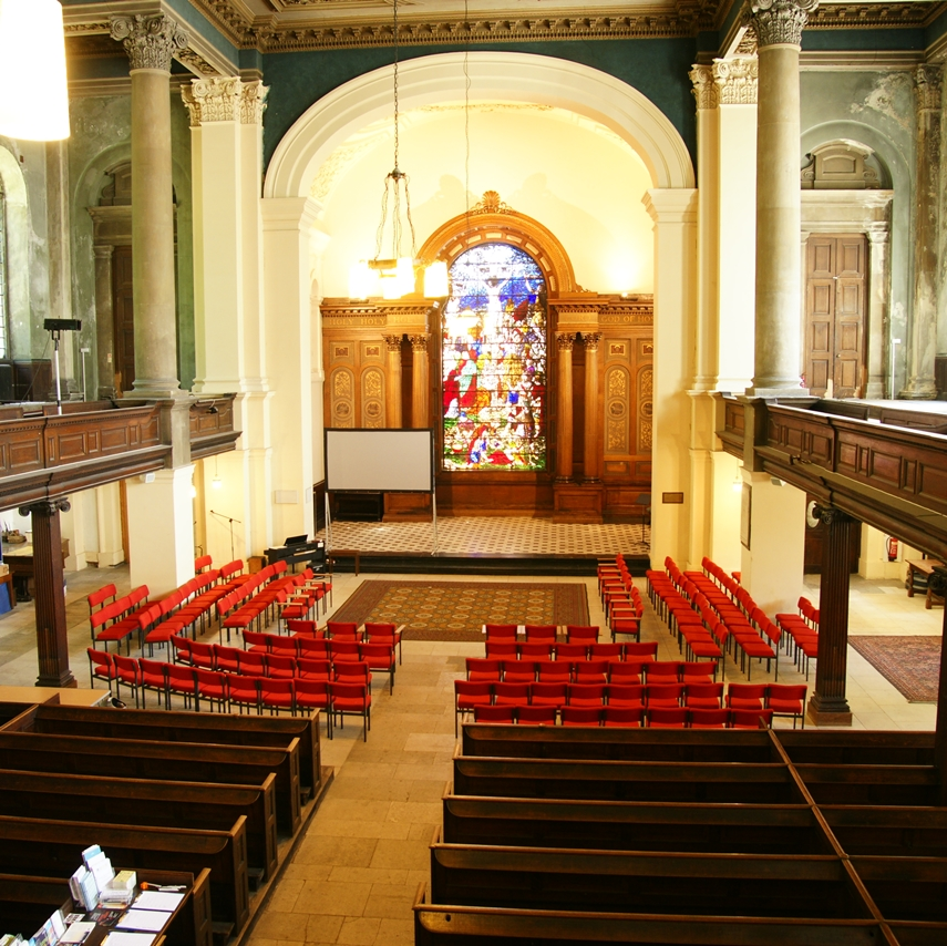 Summer 2018 view of the nave showing pews at the back of the church and chairs at the front. The east window is at the centre of the picture.